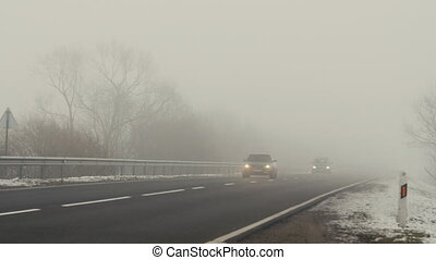 Cars ride on the road and shining lights in the fog