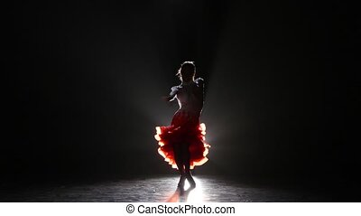 Beautiful girl dancing cha-cha-cha in the studio on a dark...
