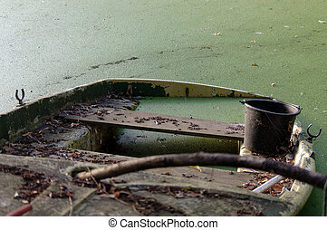 Partially sunken moored wooden rowboat with leaves.