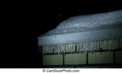 Icicles on the roof of brick building and snowfall at night super slow motion shot