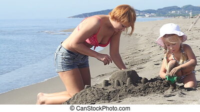 Mom and daughter are building a sand castle on the beach
