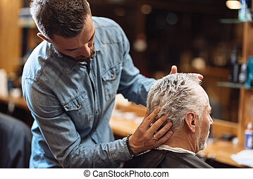 Back view of barber styling seniors client hair