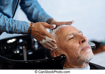Old man during washing his hair in barber shop - Perfect...
