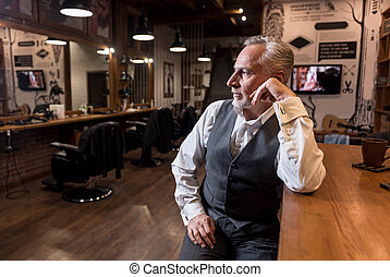 Senior businessman sitting at bar counter and looking aside...