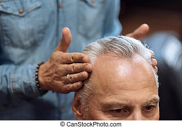 Close up of hairdresser using hair gel on client