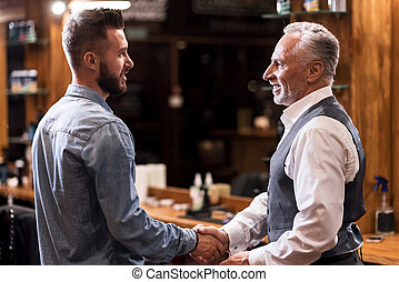 Barber and client shaking hands - Two generations. Solid...