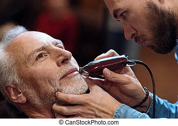 Old man getting his beard shaved by barber - Thinking over....