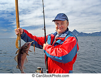 Fisherman with a fish on Lofoten island - Fisherman with a...
