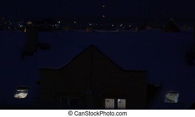 Snowy sloped roofs of residential houses at night 4K pan...