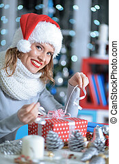Woman unwrapping Christmas present - Happy young beautiful...