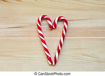 Candy Canes in Heart Shape on wooden background. Christmas