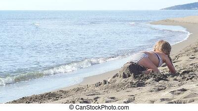 happy little girl breaks a sand castle - happy little girl...