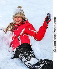 Teenager girl wearing winter clothes lying in deep snow . -...