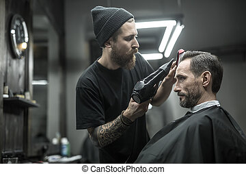 Drying hair in barbershop - Unequaled barber with a beard...