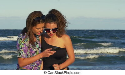 Best friends having fun on the beach with a smart phone