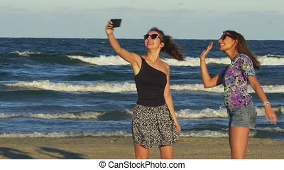 Beautiful young women having a video call conversation on the beach