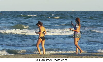 Two young beautiful women in swimsuit taking pictures with...