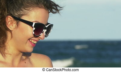 Face closeup of a young woman laughing hard by the sea