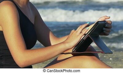 Woman writing an email on a tablet pc by the sea