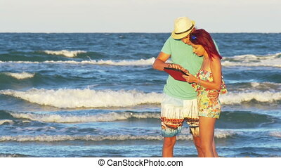 Romantic couple kissing at the seaside and holding a tablet...