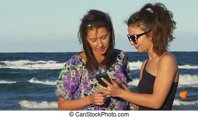 Euphoric female friends chatting and looking on a smartphone by the sea