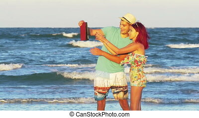 Young happy couple on the beach having video chat on tablet...