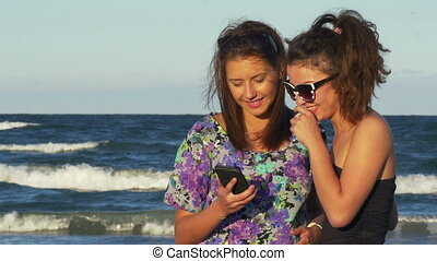 Enthusiastic friends hugging and looking at a smart phone with the sea behind