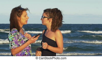 Girl talking with her best friend and looking at the smart phone on the beach