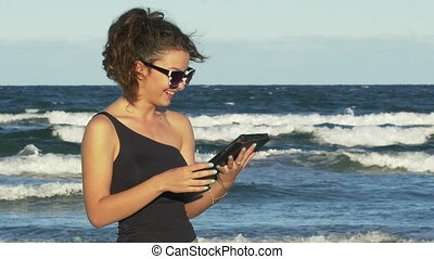 Young woman laughing and having fun with her tablet pc on the beach