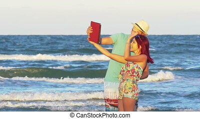 Beautiful couple keeping in touch with friends with a tablet on video call by the sea