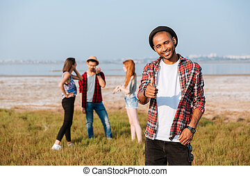 Happy man showing thumbs up while his friends talking outdoors