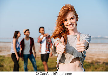 Cheerful woman showing thumbs up while her friends talking outdoors