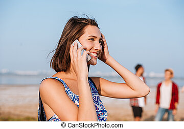 Happy woman talking on mobile phone outdoors - Happy pretty...