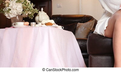 Bride near the table for tea with a rose in hand