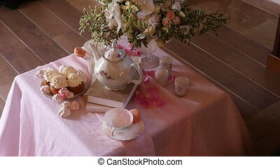 tea table decorated with flowers for the bride