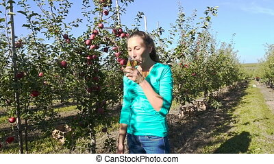 woman drinking juice in the apple orchard