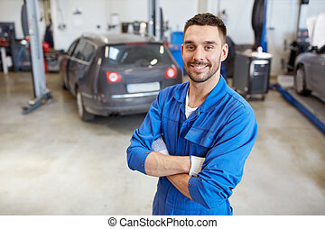 happy auto mechanic man or smith at car workshop - car...