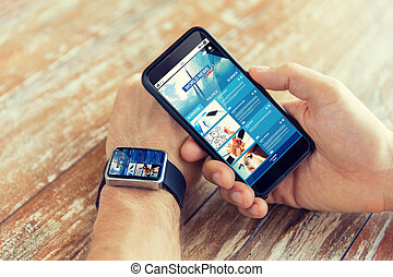 hands with news web page on smart phone and watch -...