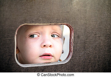 Curious kid spying through the hole in the wooden wall on playground
