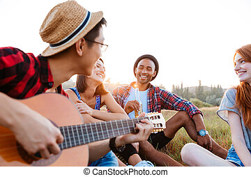 Happy young people sitting outdoors and playing guitar...