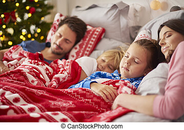 Family sleeping in Christmas morning