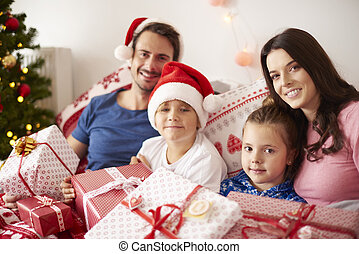 Family spending Christmas morning in bed