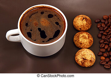 white cup of hot black coffee with biscuits and beans