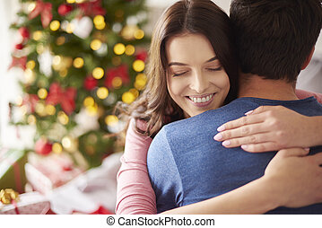 Smiling woman embracing her boyfriend in Christmas