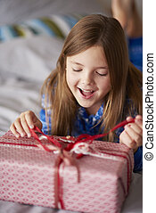 Exciting girl opening Christmas present