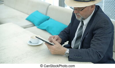 Old businessman works with tablet in cafe. 4K.
