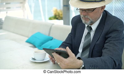 Old businessman using tablet and drinking coffee in cafe....