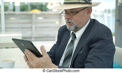 Old businessman talking via internet with tablet. 4K.