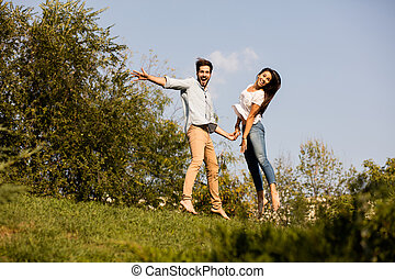 young couple jumping somewhere in nature - young happy...