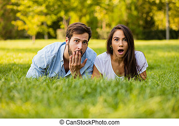 suprised couple looking to camera - surprised couple lying...